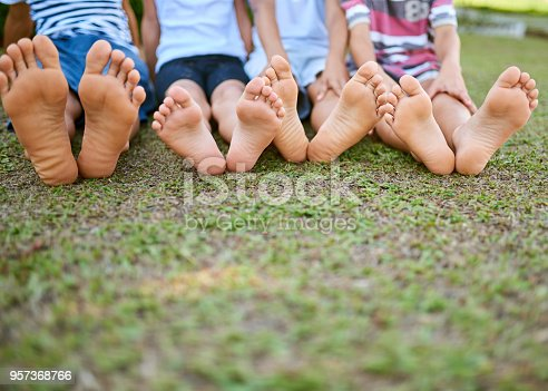 Cropped shot of a group of kids sitting barefoot on grass