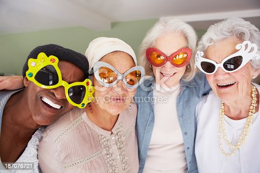 A group of elderly woman wearing funky sunglasses while standing in a nursing home