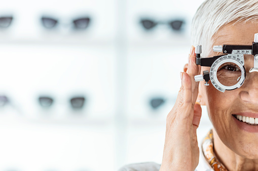 Senior beautiful woman checking her sight at ophthalmologist with Eye Test Equipment.