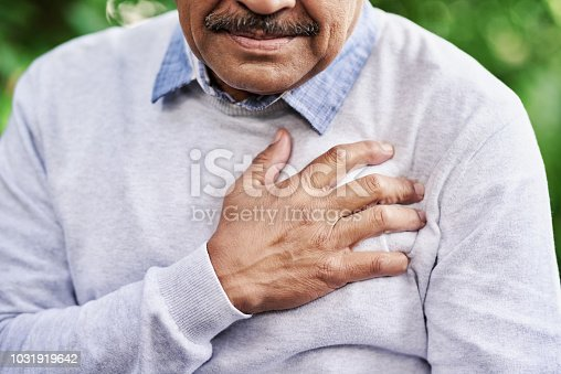 Closeup shot of a mature man holding his chest in discomfort outdoors