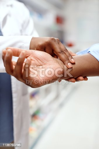 Closeup shot of an unrecognizable pharmacist checking a patient's pulse in a chemist