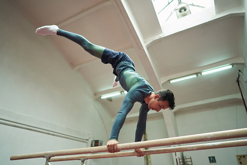 Young strong male athlete, a gymnast performing the routine on a parallel bar, during his training in the indoor gymnastic court