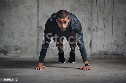 Portrait of a handsome young sportsman doing push ups while exercising inside a parking lot