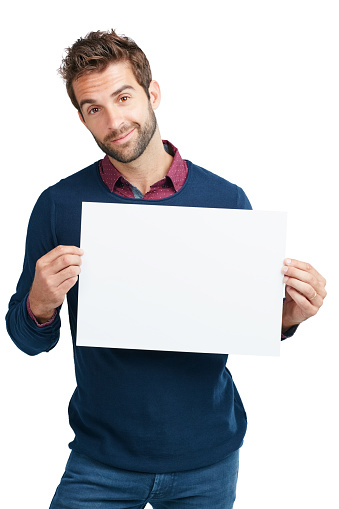 Studio portrait of a handsome man holding a blank placard against a white background