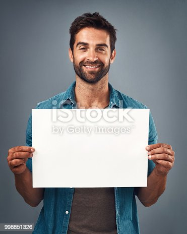 Studio shot of a handsome young man holding a blank placard against a grey background