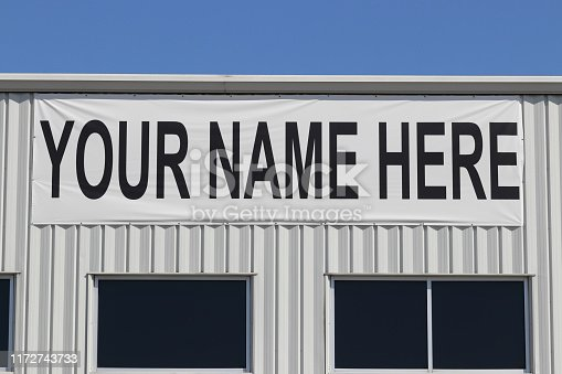 Your Name Here banner on the exterior of a vacant building for lease or rent I