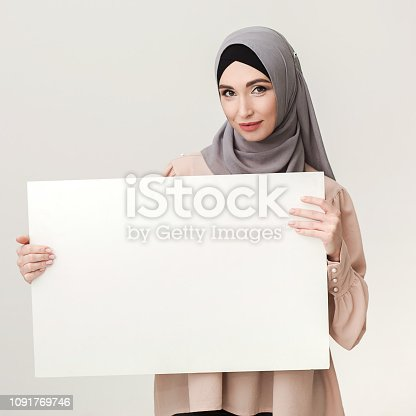 istock Your offer here. Woman in hijab holding white banner 1091769746