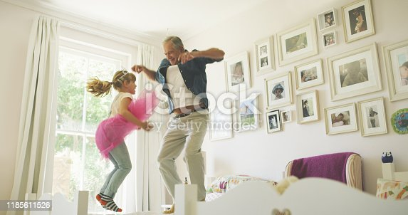 Shot of a senior man having fun with his granddaughter at home