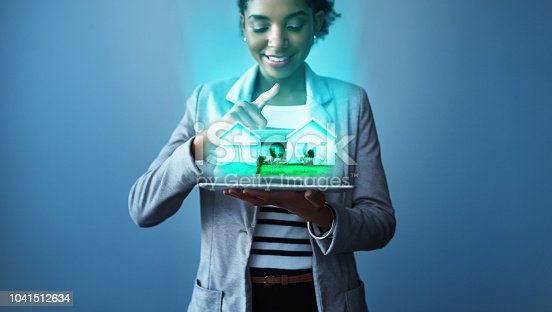 Studio shot of a young businesswoman using a digital tablet with property graphics against a blue background