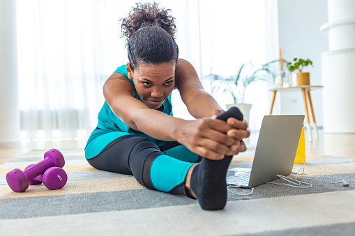 Slim sportswoman in sportswear warming-up muscles before workout doing stretching exercise sitting on floor at home