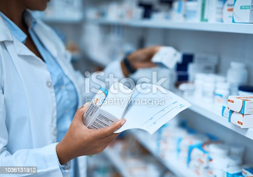 Cropped shot of a pharmacist filling a prescription at a chemist