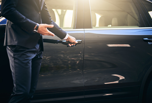 Cropped shot of a well dressed and unrecognizable man opening a car door