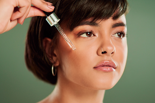 Cropped shot of a beautiful young woman holding a serum dropper against her face