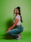 Shot of a young woman posing against a green background with a trendy hairstyle