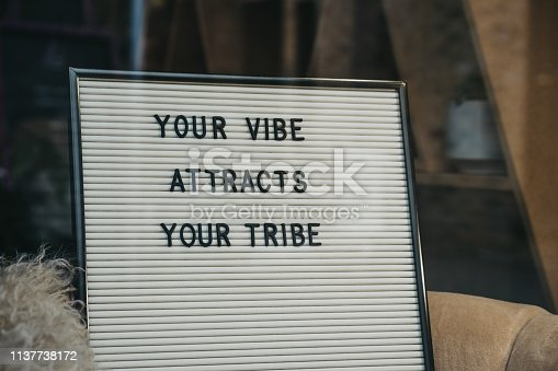 Your vibe attracts your tribe motivational quote on a white letter board.