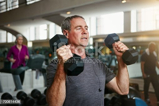 Shot of a senior man working out with weights at the gym