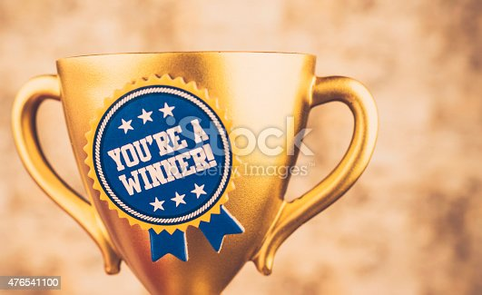 You're a winner! Gold trophy with congratulatory message. Success.