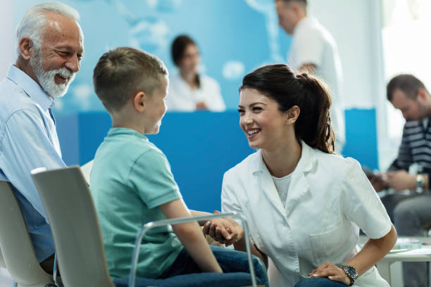 You're completely healthy, you can go home! Happy female doctor talking to a small boy who came with grandfather for an medical appointment at clinic. outpatient stock pictures, royalty-free photos & images