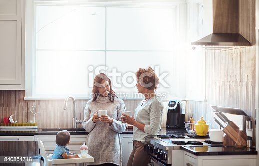 Shot of an adorable baby girl drinking bottled milk in her high chair while her mother and grandmother have coffee