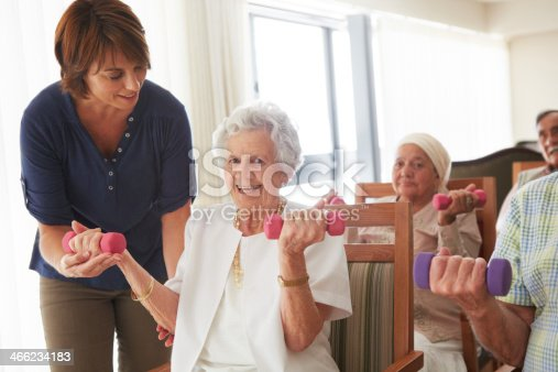 An elderly lady receiving assistance from an instructor during an exercise class at a nursing home