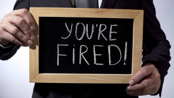 Youre fired with exclamation written on blackboard, businessman holding sign stock photo