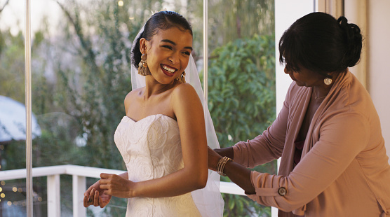 Cropped shot of a happy young bride bonding with her mother while she gets ready for her wedding