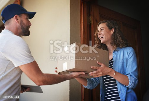 Shot of a courier making a delivery to a customer at her home