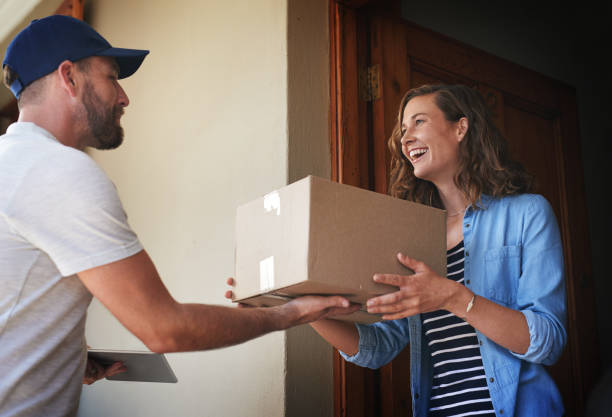 You're here quicker than I expected Shot of a courier making a delivery to a customer at her home package stock pictures, royalty-free photos & images