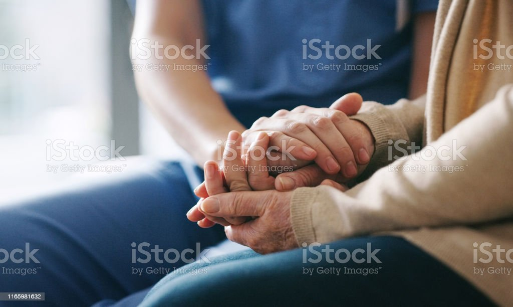 You're in a safe space now Cropped shot of a senior woman holding hands with a nurse 70-79 Years Stock Photo