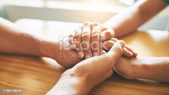 Cropped shot of a man and woman holding hands in comfort on a table