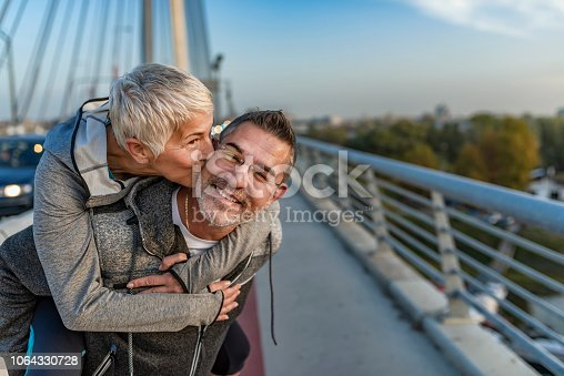 Photo of couple enjoying the outdoors together. Mature fitness  couple in love enjoying each other. Handsome  man giving a woman a piggy back ride before or after jogging in the city. Sporty Man giving his laughing wife a piggy back on the bridge on sunny day.
