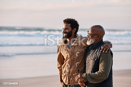 Shot of a young man going for a walk along the beach with his father