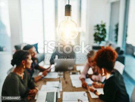 Shot of a group of young businesspeople having a meeting with a lightbulb in the foreground