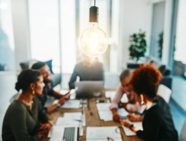 You're one meeting away from a brilliant idea Shot of a group of young businesspeople having a meeting with a lightbulb in the foreground brainstorming stock pictures, royalty-free photos & images