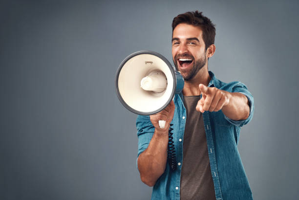 You're our winner of the day! Studio shot of a handsome young man using a megaphone against a grey background encouragement stock pictures, royalty-free photos & images