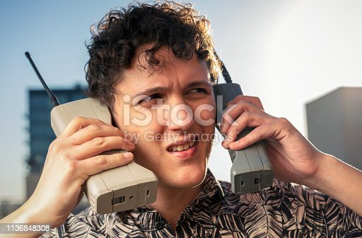 A man trying to keep up with two conversations on old-fashioned mobile phones.