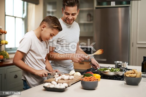 Cropped shot of a young boy helping his father cook in the kitchen