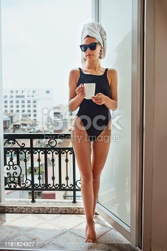 Shot of an attractive young woman posing in a black swimsuit on her balcony
