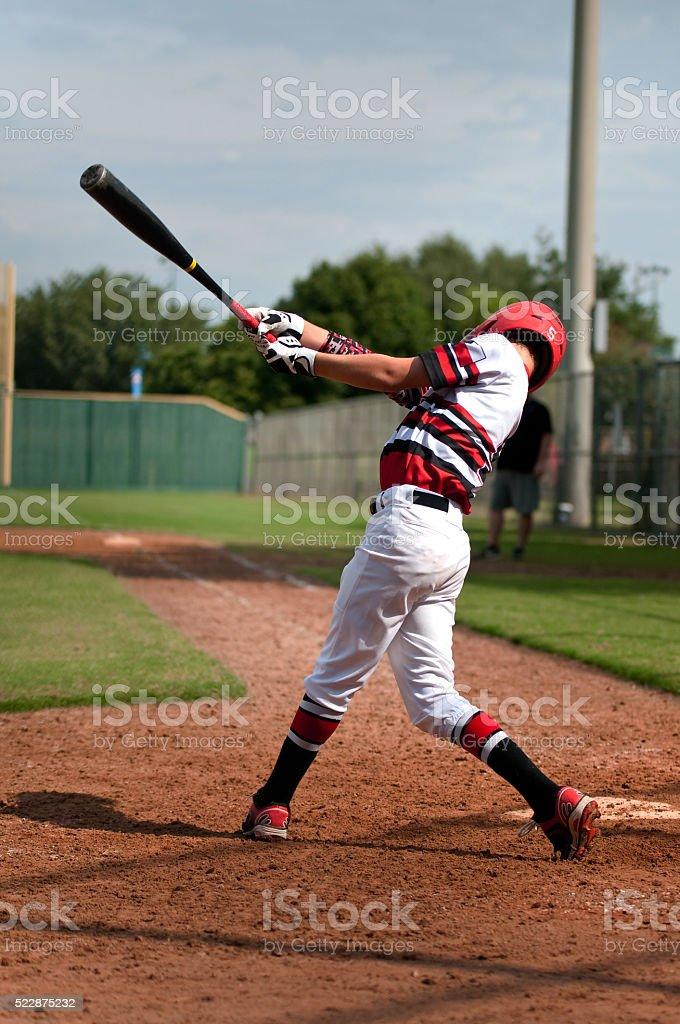 Youth baseball boy swinging bat stock photo