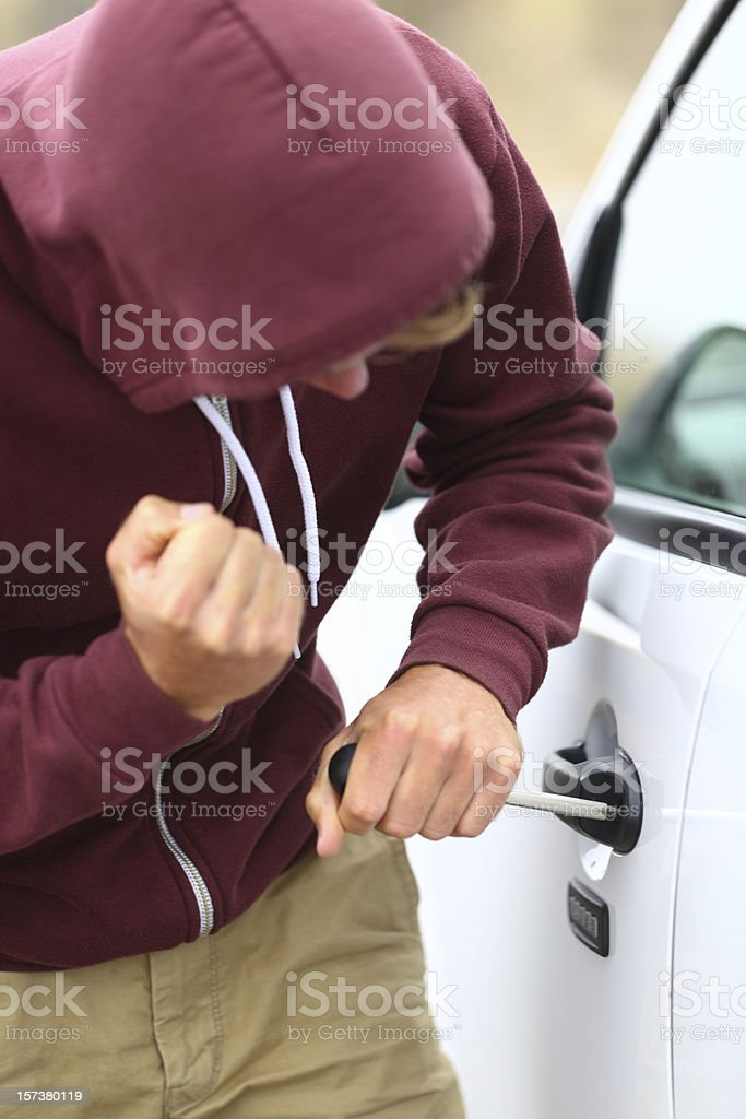 Youth breaking into a car stock photo