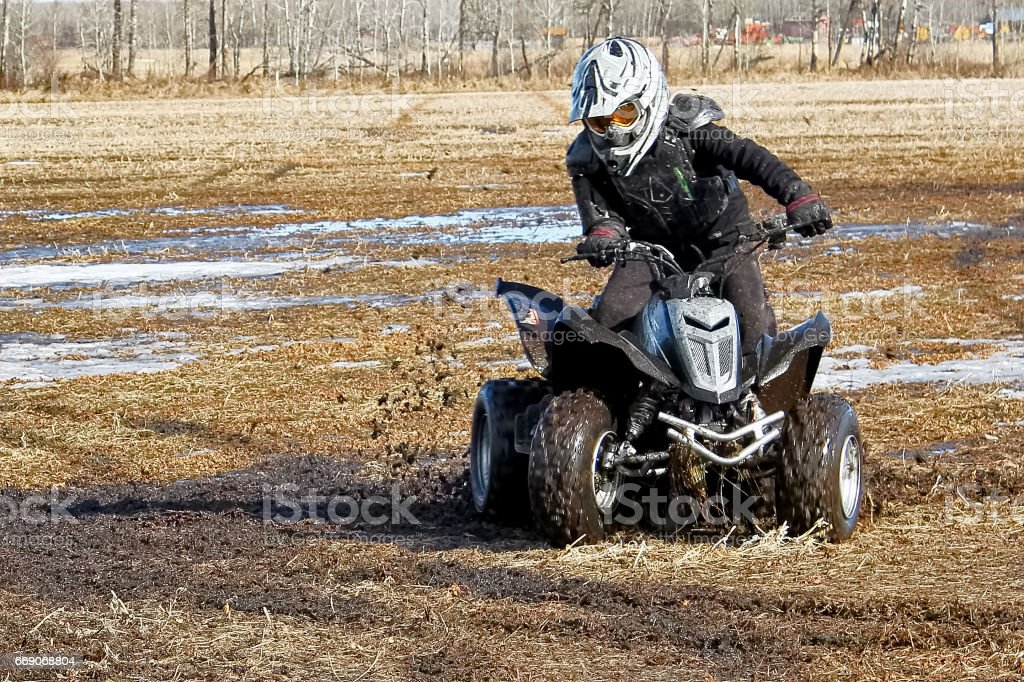 Youth doing donuts in the mud on his quad stock photo