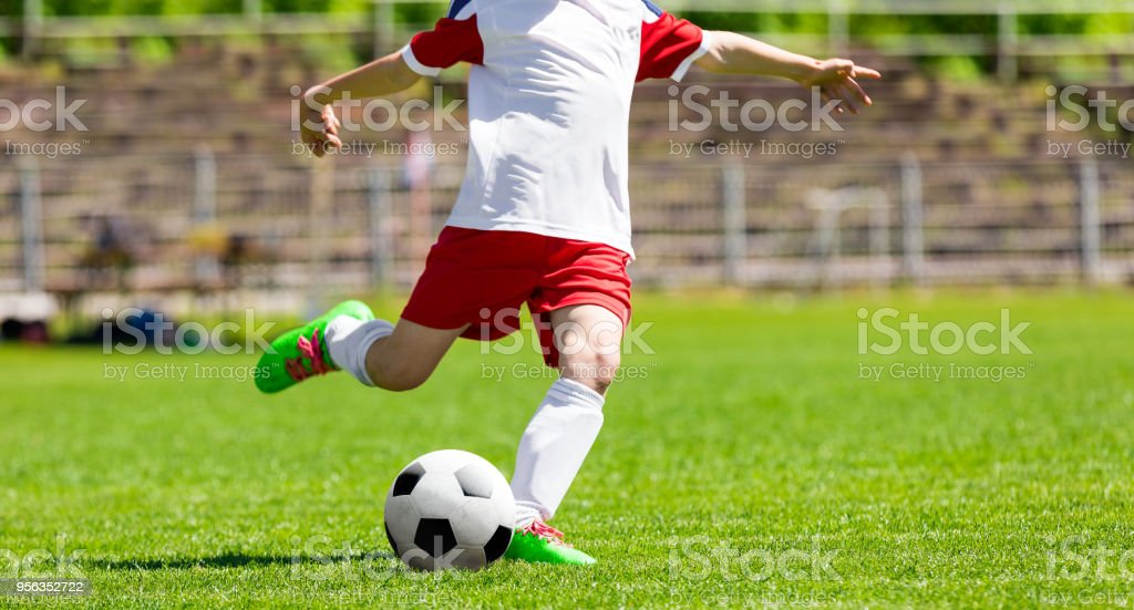 Youth Football Soccer Player Hits a Ball. Footballer Kicking Ball on Grass Pitch stock photo