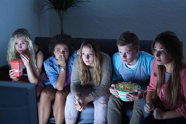 grupo de jovens em suspende ver televisão juntos - tv e familia e ecrã imagens e fotografias de stock