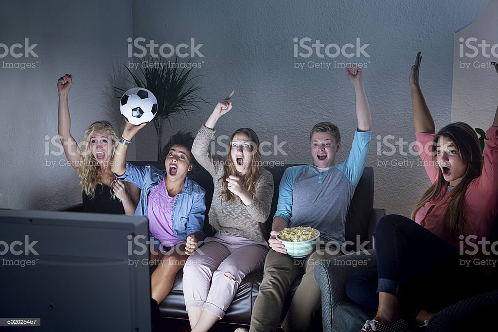 Grupo de jóvenes viendo TV juntos partido de fútbol en - foto de stock