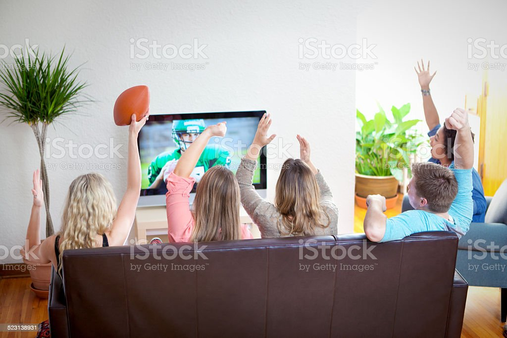 Youth Group Watching Sport Football Program on TV Together stock photo