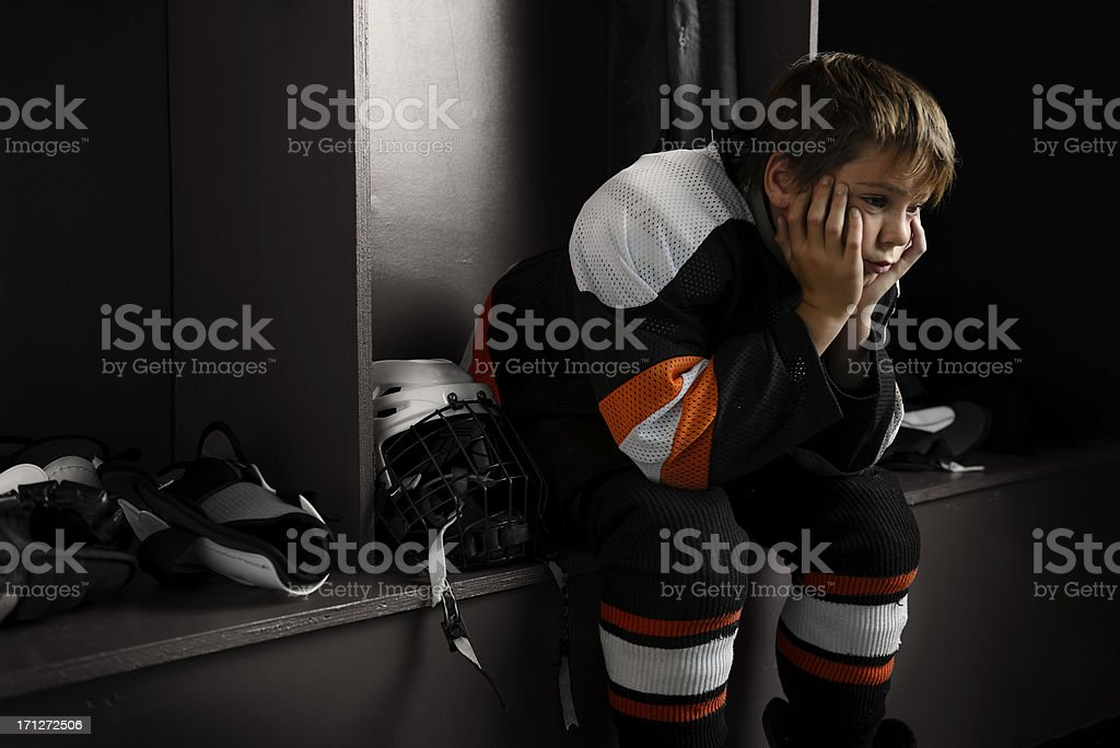 """Youth hockey player sitting in dressing room """"Portrait of a male youth hockey player sitting in the dressing room tired, after the hockey game.Click on an"""" 10-11 Years Stock Photo"""