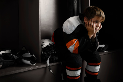 Youth Hockey Player Sitting In Dressing Room Stock Photo - Download Image Now