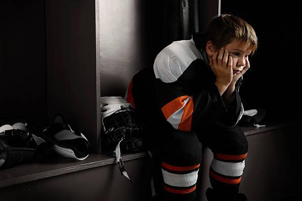youth hockey-spieler sitzen im ankleideraum - niederlage stock-fotos und bilder