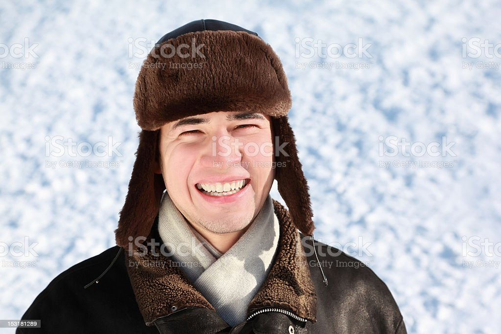 Youth in winter stands on snow and laughs stock photo