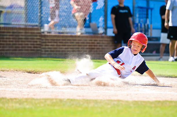 youth league baseball player sliding home. - sliding stock photos and pictures